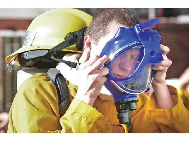 Fire trainee Michael Kutylo, 17, dons his breathing apparatus during the training exercise.