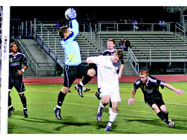 Valencia goalkeeper Daniel Adame stops a shot on goal by Canyon's A.J. Rochow, center, at Canyon High School on Friday. The game finished in a 1-1 draw, leaving the two teams tied for third place in the Foothill League with 3-2-3 records.