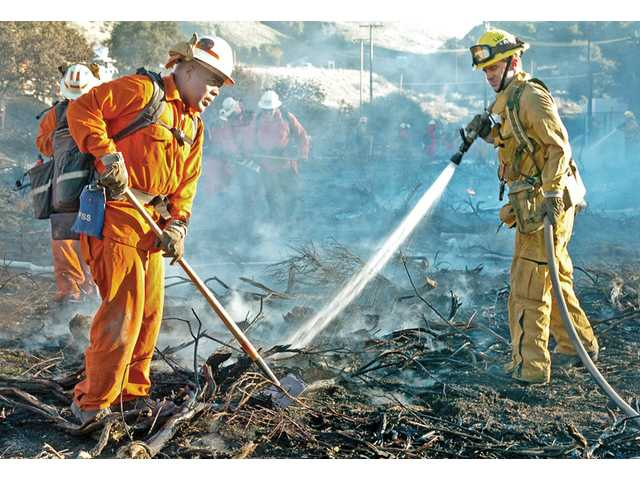Los Angeles County firefighters work to knock down flames and clear brush west of Highway 14 near Newhall Avenue in Newhall on Thursday.