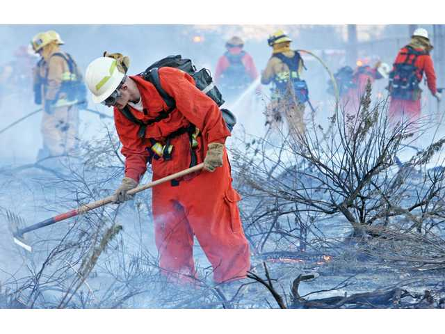 Los Angeles County firefighters work to knock down flames and clear brush west of Highway 14 near Newhall Avenue in Newhall on Thursday. Three southbound lanes on Highway 14 were closed for about an hour in the afternoon so firefighters could battle the fire that scorched approximately 1 acre along the freeway, authorities said. The fire was knocked down at 4:30 p.m., less than an hour after it erupted, said officials from the L.A. County Fire Department.