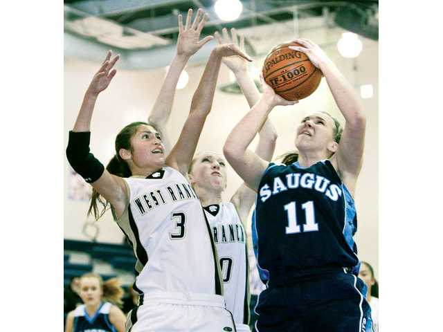 Saugus' Megan Dawe (11) shoots as Wildcats Kaylie Fandino (3) and Hannah Green defend on Thursday at West Ranch.