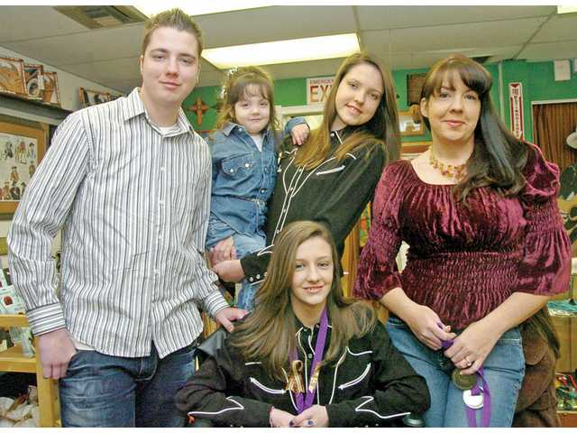 Kari Hewitt, right, poses with some of her children. From left: Andrew, 20, McKenna, 3, Emily, 17, and Sarah, 15, at front. Hewitt's new business, Serendipity Lights, offers Lit Spirit bottles priced from $38 to $60 at OutWest as well as online. Hewitt also handcrafts custom orders. The small business has also attracted the support of neighboring Newhall businesses El Trocadero and Pulchella Winery. The companies donate bottles to Hewitt to craft into gifts.