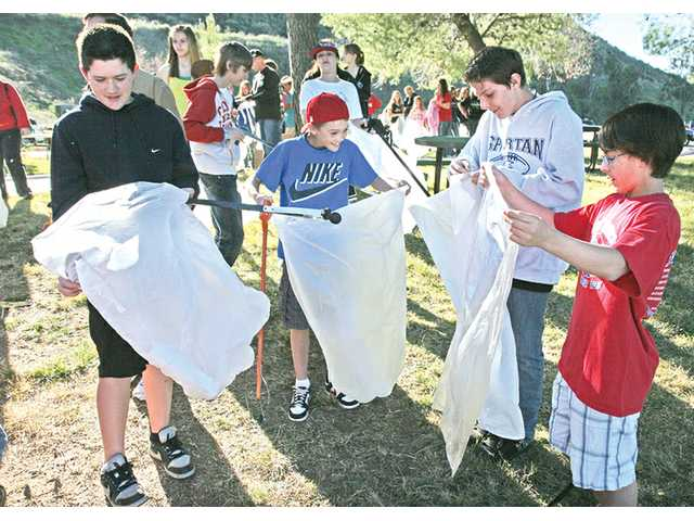 (From left to right) Arroyo Seco Junior High students Andrew Auster, 12; Ryan McClenahan, 12; Cameron Comes, 13; and Zach Preciado, 13, are issued trash bags as they join nearly 200 volunteers in picking up garbage as part of the Friends of Castaic Lake cleanup event in Castaic on Saturday.