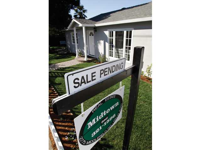 In this recent photo, a pending sale sign is posted outside a home in Palo Alto, Calif. The National Association of Realtors said Jan. 27 that its index of sales agreements for previously occupied homes rose 2 percent in December 2010, marking the fifth increase in the past six months.