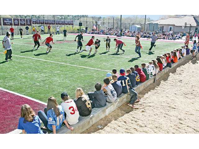 Students, faculty and parents watch a football game between faculty members and eighth-grade students at Legacy Christian Academy in Valencia on Friday. The school also dedicated the new artificial-turf football field.