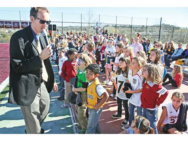 Legacy Christian Academy activities director Matt Millett, left, leads first- and second-grade students onto the new football field for the dedication ceremony in Valencia on Friday. Chamber ambassadors, local dignitaries and donors joined the student body and faculty in a celebration of their new turf. The ribbon-cutting ceremony marked a joint effort of several Legacy families who donated $140,000 collectively and gave their time and energy to make the turf dream a reality.