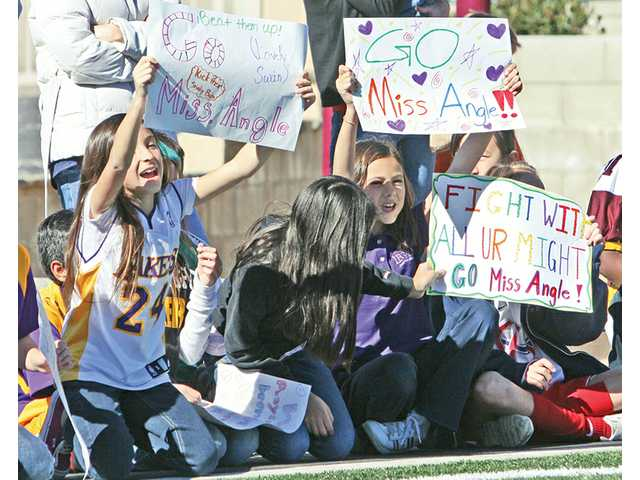 Fifth-grade students cheer on their assistant teacher Steffi Angle during the faculty versus eight-graders inaugural football game, which was played on the new artificial-turf football field at Legacy Christian Academy in Valencia on Friday.
