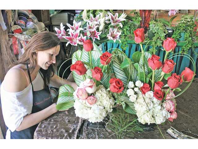 Michelle Franchino, a designer for Claire's Flowers, puts finishing touches Saturday on Valentine's Day flower arrangements containing roses and hydrangeas.