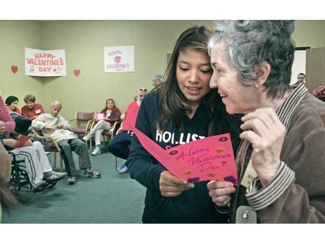 Opportunities for Learning student Gina Ballesteros, 15, left, reads a poem from her handmade Valentine's Day card to Mary Lou Schork, right, at the Santa Clarita Adult Day Health Care Center in Canyon Country on Monday. Five of the Canyon Country charter school's student council members delivered their handmade cards to each of the 40 participants at the center.