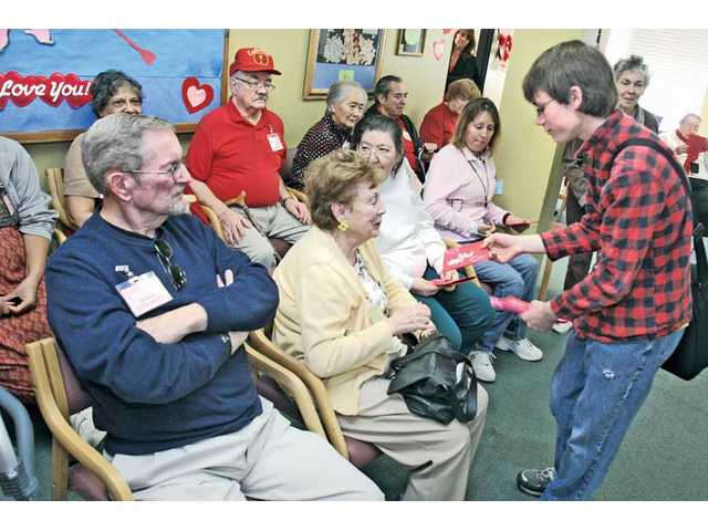 Student council member Ryan McPeters, 14, right, hands out handmade Valentine's Day cards to each of the seniors at the center.