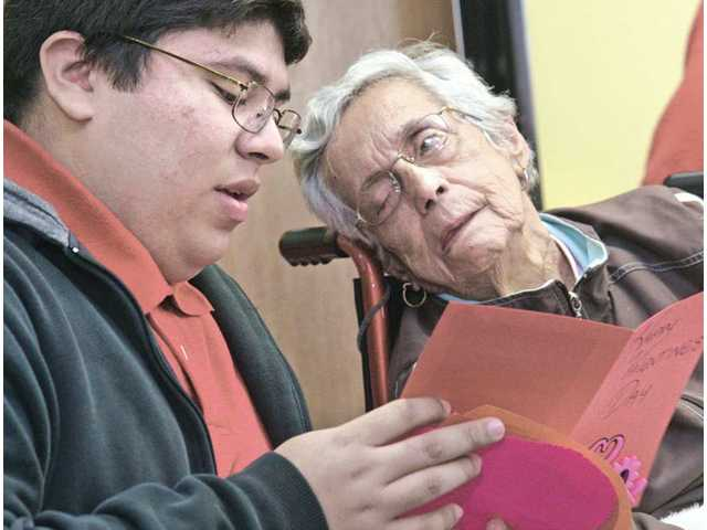Opportunities for Learning Student Council member Isaac Recinos, 18, left, reads his Valentine's Day card in Spanish to Haidee Del Hierro at the Santa Clarita Adult Day Health Care Center in Canyon Country on Monday.