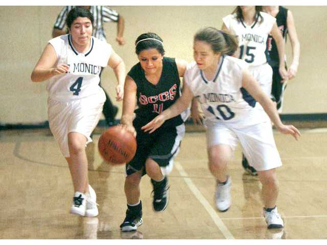 Santa Clarita Christian's Taylor Cubas (11) dribbles through the pressure of St. Monica's Deanna Shahverdian (4) and Rosario Miranda, right, at SCCS on Tuesday.