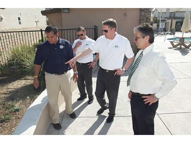 Brad Watson, managing director of Property Management Professionals (pointing), discusses maintenance of an HOA-maintained common area with Greg Marques, far left, Kevin Harbison, near left, and Alex Woltman, right.