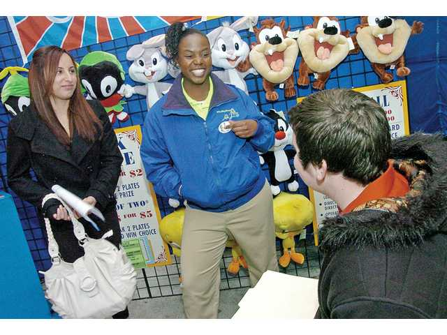 Angel Oliver, 19, middle, relates her three years of experience as a games hostess to Juanita Loza, 18, left, and Pat O'Brien, 16, at Six Flags Magic Mountain on Saturday. A job fair there drew thousands.