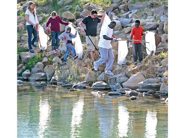 Some of the 175 volunteers for the Friends of Castaic Lake cleanup event scan the shoreline of the lower lagoon for trash at Castaic Lake in Castaic on Saturday.