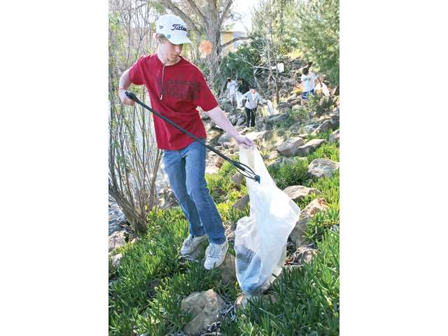 Ryan Roach, 15, of Saugus, picks up trash as part of the Friends of the Castaic Lake cleanup event.