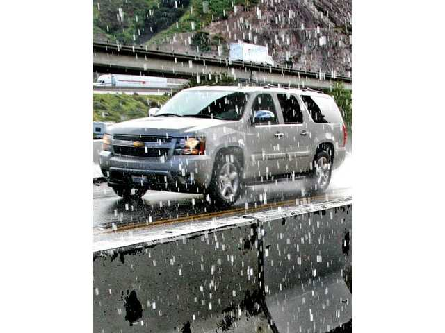 Water pours down on an SUV on The Old Road near Sierra Highway on Wednesday, as it passes under a Highway 14 overpass still under construction, which funneled water onto vehicles below due to heavy rains.