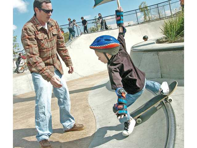 Henry Reasner, 5, right, stumbles as his father, Dave, teaches him how to skateboard at Santa Clarita Skatepark in Santa Clarita on Monday.