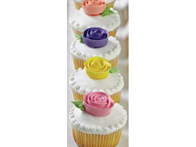 Blooming cupcakes: A colorful ribbon rose adds the finishing touch to these party cupcakes. The ribbon rose is a new addition to the Wilton curriculum and offers a contemporary twist to the classic piped rose.