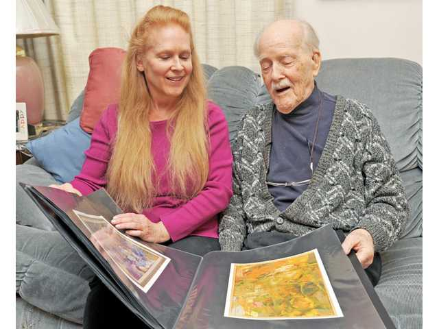 Geraldine Livingston, left, and her father, Harold Olov Wang, 99, look over a portfolio of Wang's work at his home in Friendly Valley in Canyon Country on Wednesday. Livingston is helping her father sell his paintings online at www.haroldolovwang.com.