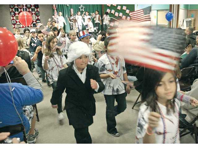 "Nicholas Shimada, center, wears a white wig to portray Thomas Jefferson, as his third-grade class exits the stage to ""The Washington Post"" march by John Philip Sousa. The procession came at the end of the ""Proud to be Americans"" performance at Castaic Elementary School on Thursday."