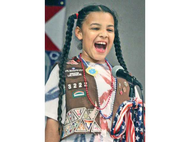 "Third-grader Heather Griffiths sings Irving Berlin's ""God Bless America."""