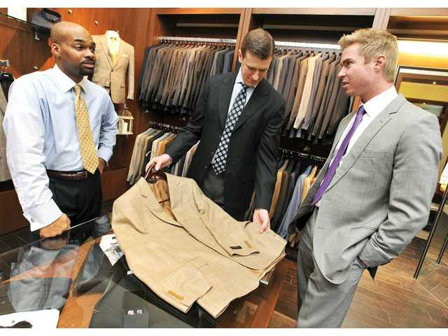 David Guenther, president of J. David's Custom Clothiers, left, and Dr. Chace Unruh, a Valencia-based chiropractor, look through fabric swatches at Guenther's store at The Patios at Valencia Town Center on Friday. Guenther purchased the business that became J. David's in 1988.