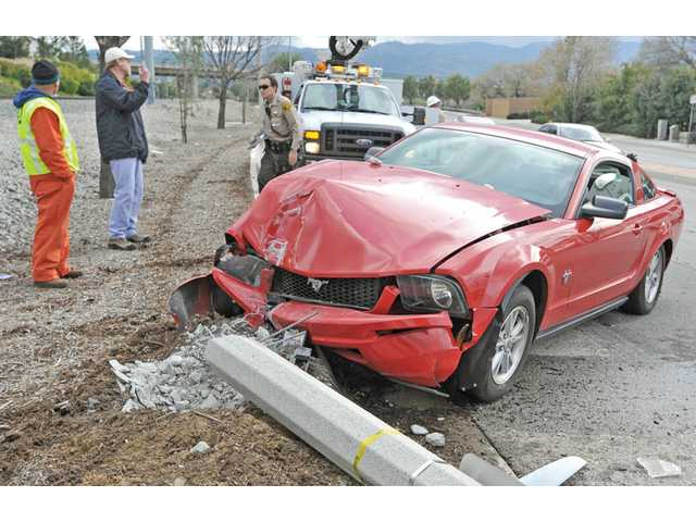 Authorities respond to a single-vehicle crash on the northbound side of Railroad Avenue, south of Oak Ridge Drive, in Newhall on Wednesday. The driver of the Mustang was transported to a hospital with unknown injuries, according to a Los Angeles County sheriff's deputy on the scene. The driver was not believed to be under the influence, the deputy said.