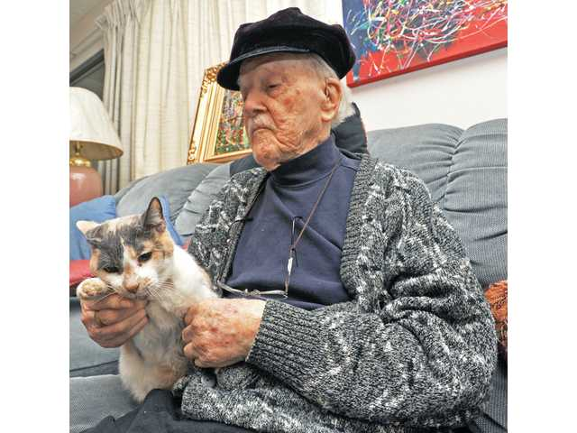 Harold Wang, 99, plays with his cat Calico at his home in Friendly Valley on Wednesday.