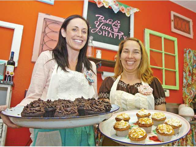 Kim Thurman, left, and Kim Aeck of Bake You Happy show off their double chocolate and caramel apple cupcakes at their new store in Valencia.