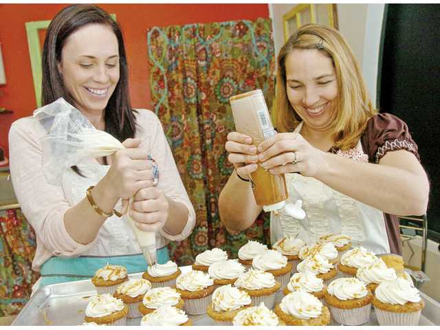 "Kim Thurman, left, and Kim Aeck of Bake You Happy put the finishing touches on a batch of caramel apple cupcakes. The duo won $10,000 in the reality competition show ""Cupcake Wars"" on the Food Network. The show was taped in November and shown in January."