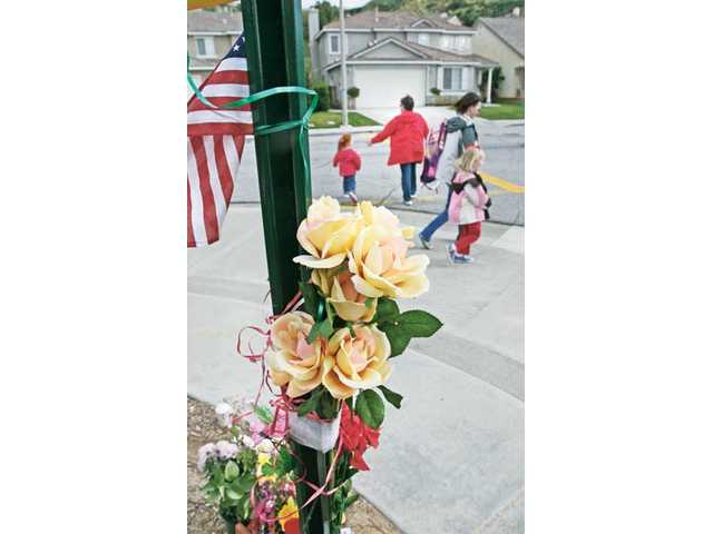 Mountainview Elementary School students cross the street in front of a memorial for popular crossing guard Kenneth Campbell at the corner of Garnet Canyon Drive and Cypress Place in Saugus on Wednesday. The memorial was put in place after Campbell died on Feb. 12.