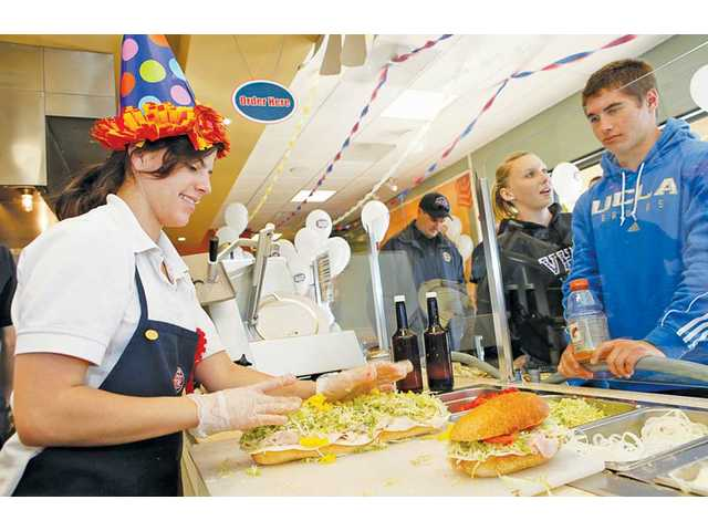 Jersey Mike's employee Kyanna Isaacson, 19, makes a sandwich for Steven Manfro, 18, of Valencia, during the shop's third anniversary celebration on Saturday in Saugus. The store is one of 50 locations in California for the East Coast-based sandwich shop.