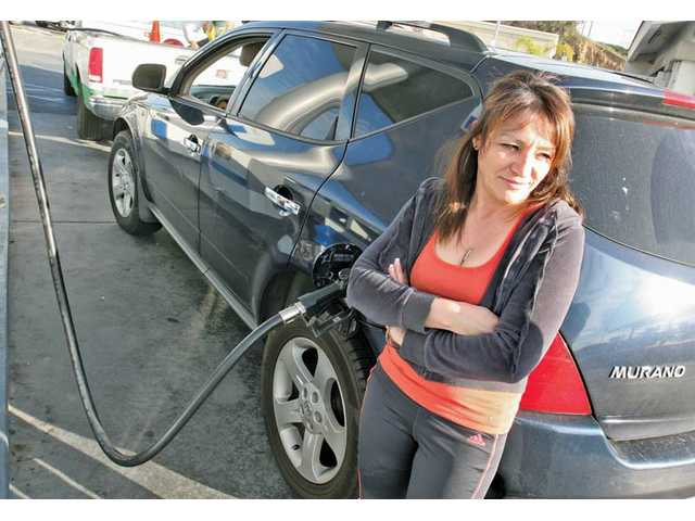 Irma Martinez, of Newhall, fills her Nissan SUV at the Chevron station at Bouquet Canyon and Soledad Canyon roads in Valencia on Tuesday. Gasoline prices have risen across the country in recent weeks, fueled in part by concerns over future supplies due to the current unrest in the Middle East.