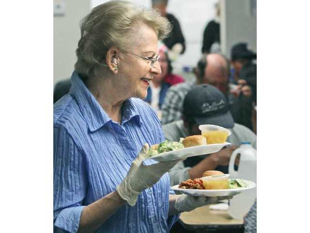Lolly Leathers serves clients at the Santa Clarita Emergency Winter Shelter in Saugus on Tuesday night. Shelter officials said recently that tough economic conditions leave the facility's beds near capacity every night.