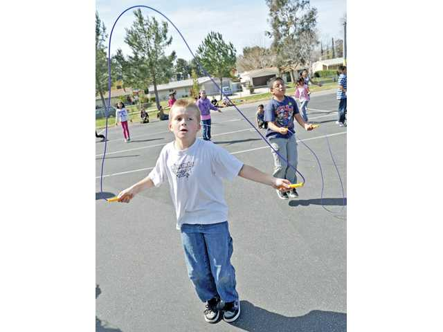 Fifth-graders Shane Halstead, 10, front, and Ruben Montano, 10, jump rope in competition for prizes.