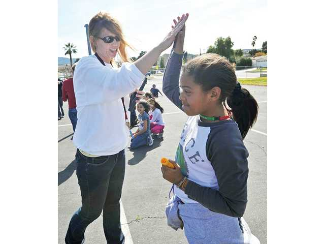 Teacher Gretchen Lupica, left, high-fives Taylor Henry, 9, at the Jump Rope for Heart event at Canyon Springs Community School in Canyon Country on Friday.
