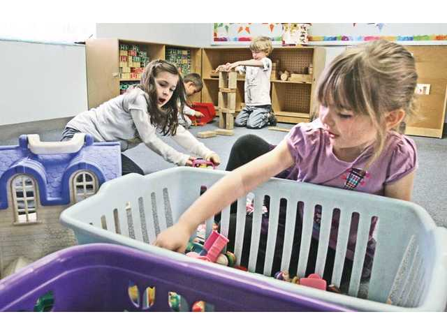 Preschoolers Kalea Lopez, 5, left, and Allyanna Blaha, 5, pick toys from a bin as they play house at Little Shepherd's Nursery School in Newhall on Wednesday.