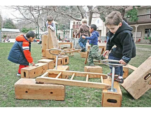 Students ages 4 to 5 use building blocks in the playground.