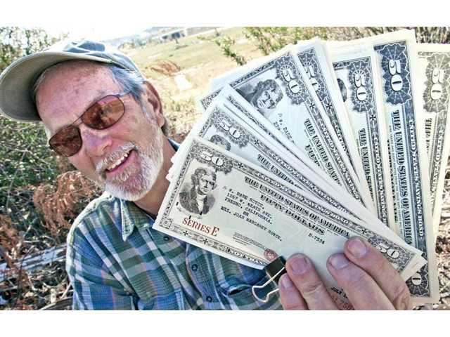 Rick Steinbruecker displays $15,000 of savings bonds Friday at the Santa Clara River in Canyon Country. Steinbruecker found the savings bonds, along with the paper history of a California family, in a file cabinet on the riverbed five years ago. The find is one of many the man has made in the river.