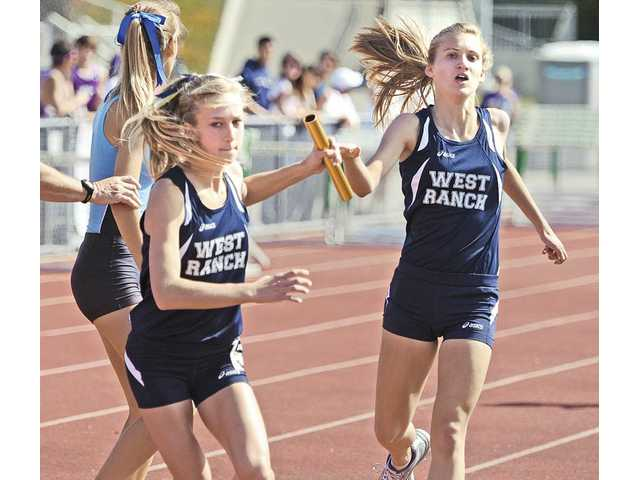West Ranch's Taylor Welker, left, takes the baton from Samantha Phillips in the 4x1600-meter relay Saturday at Canyon High.