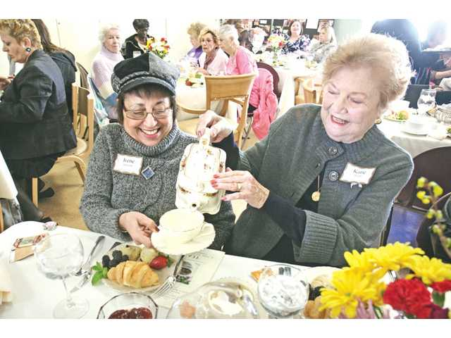 Katie Werft, right, pours hot water for Irene Jansson during the Survivor's Tea at the SCV Senior Center recently.