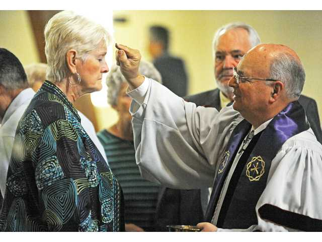 Ellie Lacy, left, receives a cross of ash on her forehead from Stan Fix, pastor of Friendly Valley Community Church. The ashes are part of the Imposition of Ashes as a part of the Ash Wednesday service at the church in Newhall on Wednesday.