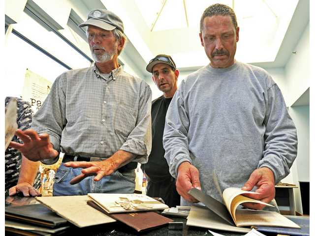 From left, Rick Steinbruecker, Brian Caballero, and Ken Royce sift through old documents that Steinbruecker found in a filing cabinet at The Signal's office in Valencia on Wednesday.