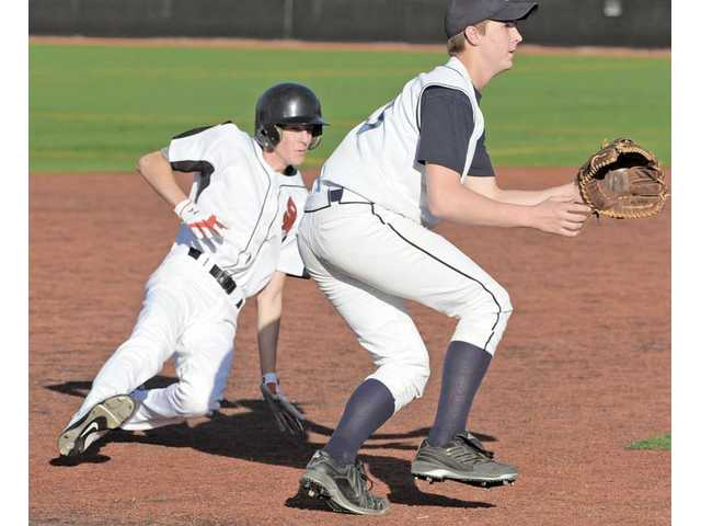 Santa Clarita Christian's Davis Muxlow, left, steals third base and beats the throw to Frazier Mountain's Casey Holcomb on Wednesday at Reese Field at The Master's College.