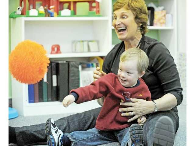 Greenhouse Tutoring Center founder Joan Green tosses a ball with student Michael Meyer, 3, of Valencia.