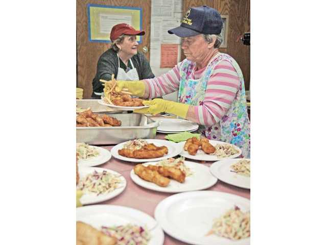 Volunteer Paulette Ballock, right, places french fries on a plate during the first Friday of St. Clare of Assisi Roman Catholic Church's Lenten Fish Fry event on Feb. 19, 2010, in Canyon Country.