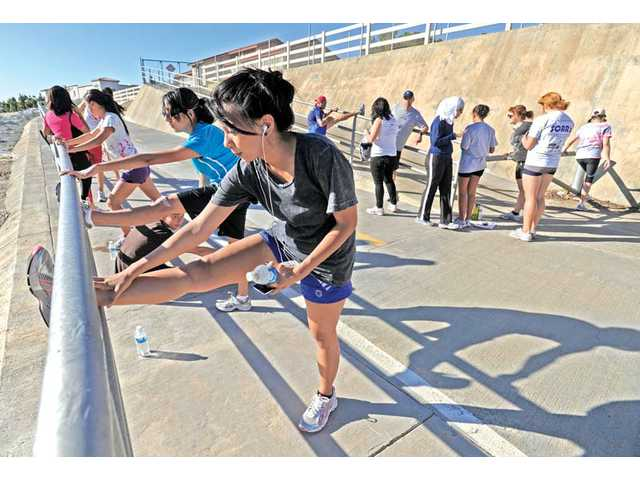 Canyon High School student Charmaine Sadia, 18, foreground, stretches with a group of local student participants of the SOAR program before a five-mile run on a Santa Clarita paseo on Thursday. The group is training for the L.A. Marathon.