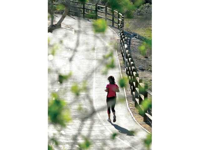 Stephanie Velazquez, 16, makes a five-mile run on a Santa Clarita paseo on Thursday as part of the SOAR training program. The members of the local running club say the group's training and exercise have helped them learn to focus in the classroom, as well.