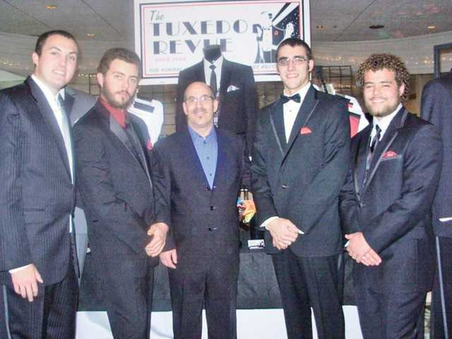 Tuxedo Revue owner Jeffrey Globerman, center, with, from left, Andrew Farrell, Riley Bowers, Loren Bowers and Wesley Bowers at a bridal show at the Knollwood Country Club in Granada Hills in December. On average, Tuxedo Revue, of Newhall, offers an inventory of approximately 400 to 500 suits.
